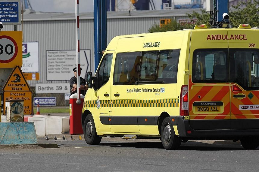 An ambulance arrives at Tilbury Docks, east of London on Aug 16, 2014, where one man was found dead and 19 people, including seven children, were discovered inside a shipping container.A man was arrested in Northern Ireland on Tuesday, Aug 19,