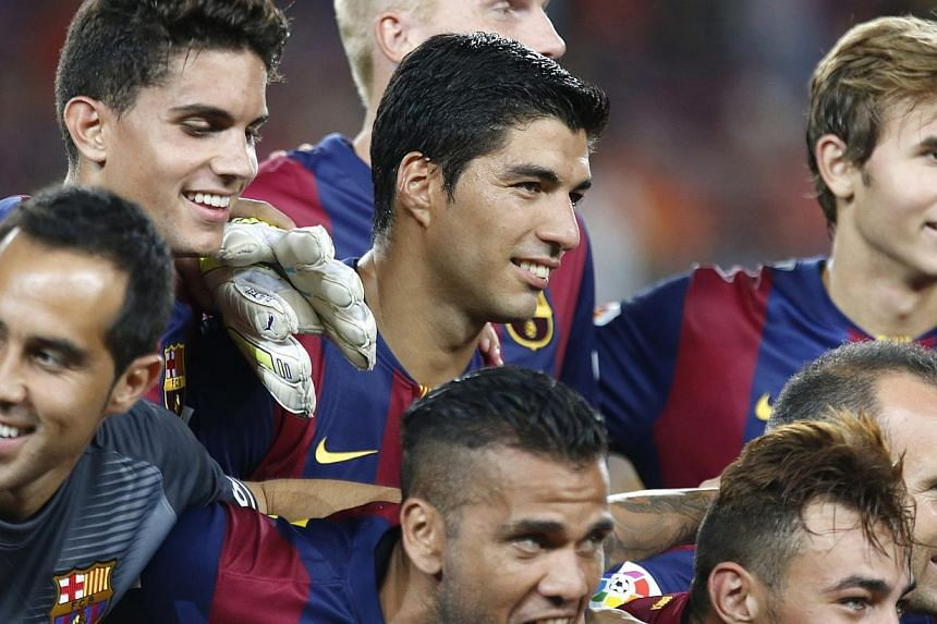 Barcelona's Luis Suarez (centre) celebrates with teammates after winning the Joan Gamper Trophy soccer match against Mexico's Club Leon at Nou Camp stadium in Barcelona on Aug 18, 2014. -- PHOTO: REUTERS