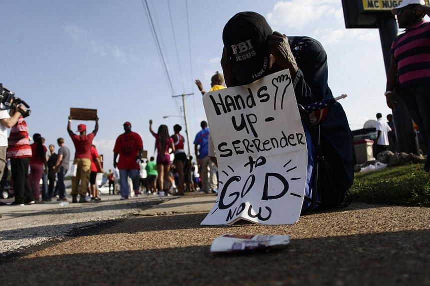 A demonstrator kneels and prays during a protest against the shooting death of Michael Brown. -- PHOTO: REUTERS