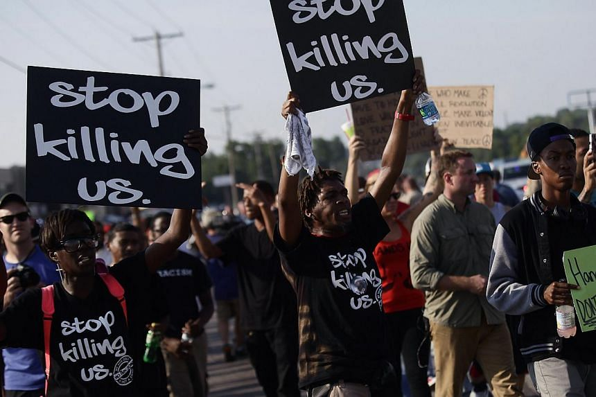 Demonstrators holding signs protest against the shooting death of Michael Brown . -- PHOTO: REUTERS