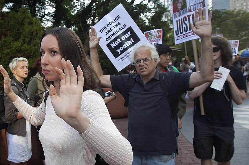 Protesters walk with their hands up as they participate in a protest against the police in Ferguson, Missouri, in the Manhattan borough of New York. -- PHOTO: REUTERS