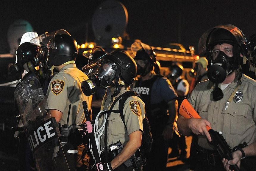 """Law enforcement offices watch on during a protest on West Florissant Avenue in Ferguson, Missouri on Aug 18, 2014.The police came under """"heavy gunfire"""" and 31 people were arrested, the authorities said on Tuesday, in racial unrest in Ferguson,"""