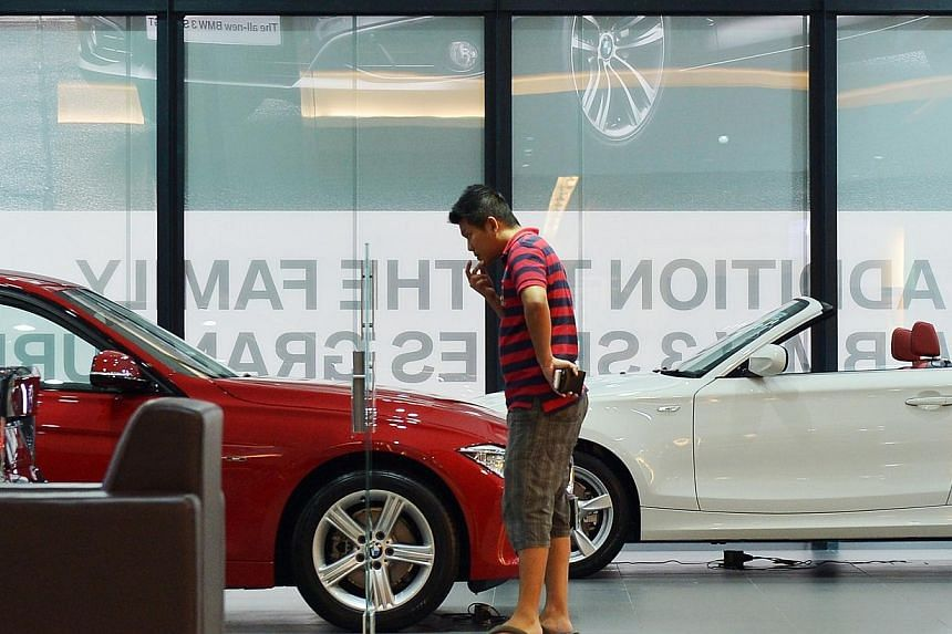 A customer lookiing at a BMW 316i at the Performance Motors showroom on Alexandra Road on 9 September 2013.Certificates of entitlement (COE) for cars all ended higher at the latest tender on Wednesday. -- PHOTO: ST FILE