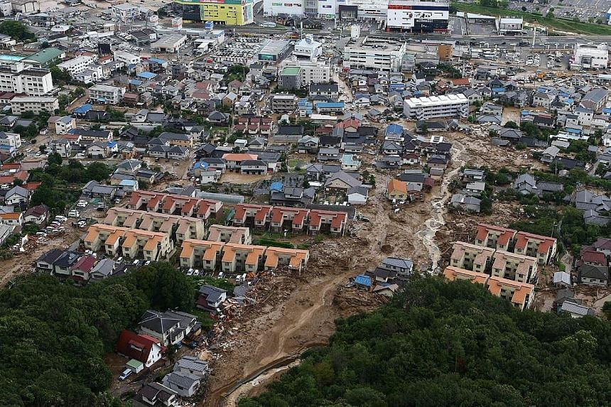 This aerial view shows the damage caused by a landslide after heavy rains hit the city of Hiroshima, western Japan, on Aug 20, 2014.A huge landslide that engulfed homes in western Japan killed at least 39 people and left another seven missing,