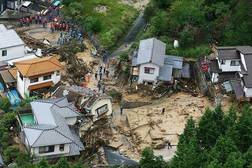 This aerial view shows policemen and rescue workers looking for survivors at a landslide site after heavy rains hit the city of Hiroshima, western Japan, on Aug 20, 2014.A huge landslide that engulfed homes in western Japan killed at least 39 p