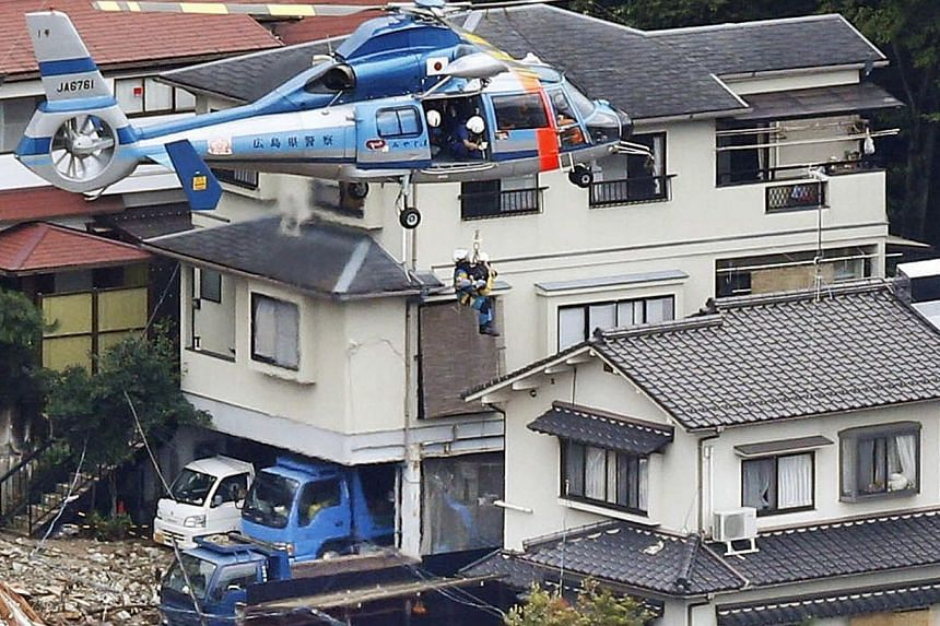 A local resident is lifted by a rescue helicopter from an area where a landslide swept through a residential area at Asaminami ward in Hiroshima, western Japan, in this photo taken by Kyodo Aug 20, 2014.A huge landslide that engulfed homes in w