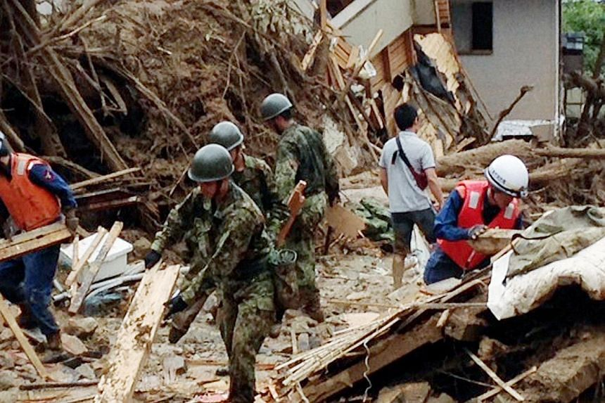 This handout picture taken by Japan's Joint Staff shows soldiers and rescue workers looking for survivors at the site of a landslide after heavy rains hit the city of Hiroshima, western Japan, on Aug 20, 2014.A huge landslide that engulfed home