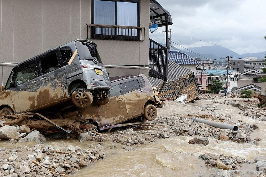 Cars damaged by a landslide lie in mud and debris after heavy rains hit the city of Hiroshima, western Japan, on Aug 20, 2014.A huge landslide that engulfed homes in western Japan killed at least 39 people and left another seven missing, the go