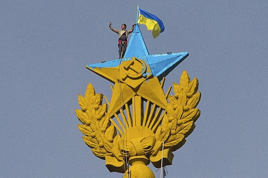 A man takes a selfie as he stands with a Ukrainian flag on a Soviet-style star re-touched with blue paint so it resembles the yellow-and-blue national colours of Ukraine, atop the spire of a building in Moscow on Aug 20, 2014.-- PHOTO: REUTERS