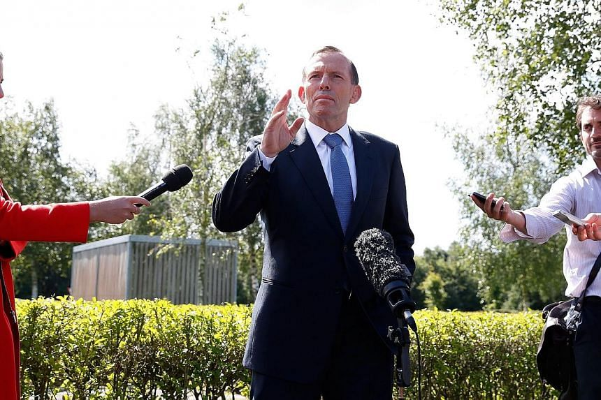 """Australian Prime Minister Tony Abbott (centre) speaks to journalists during a visit at Eindhoven's airbase on Aug 11, 2014.A new underwater hunt for missing Malaysia Airlines Flight MH370 had a """"reasonable chance"""" of finding the plane, Australi"""