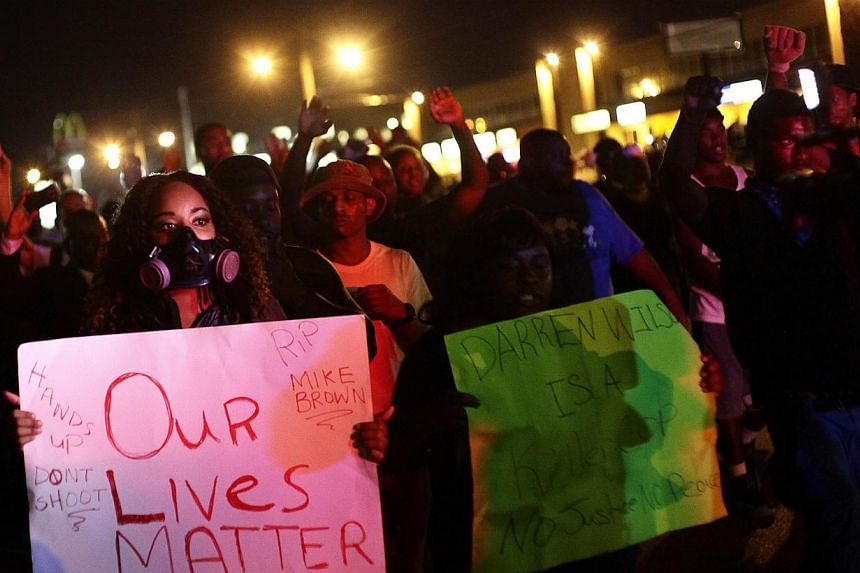 Demonstrators protest the shooting death of Michael Brown, in Ferguson, Missouri on Aug 19, 2014. Protesters hit the streets of the US town roiled by days of unrest over the killing of an unarmed black teen, hours after police shot dead a knife-