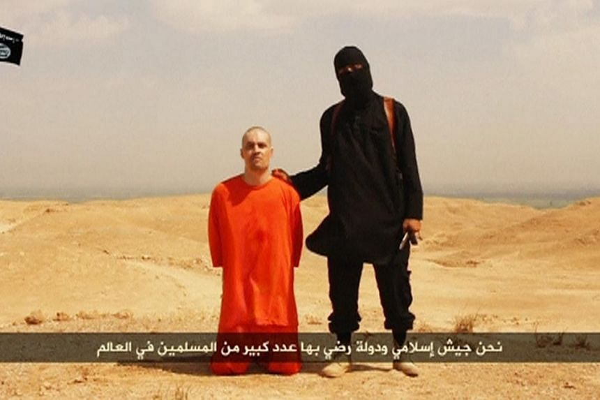 A masked Islamic State militant holding a knife speaks next to man purported to be US journalist James Foley at an unknown location in this still image from an undated video posted on a social media website. Foley'smother said on Tuesday that h