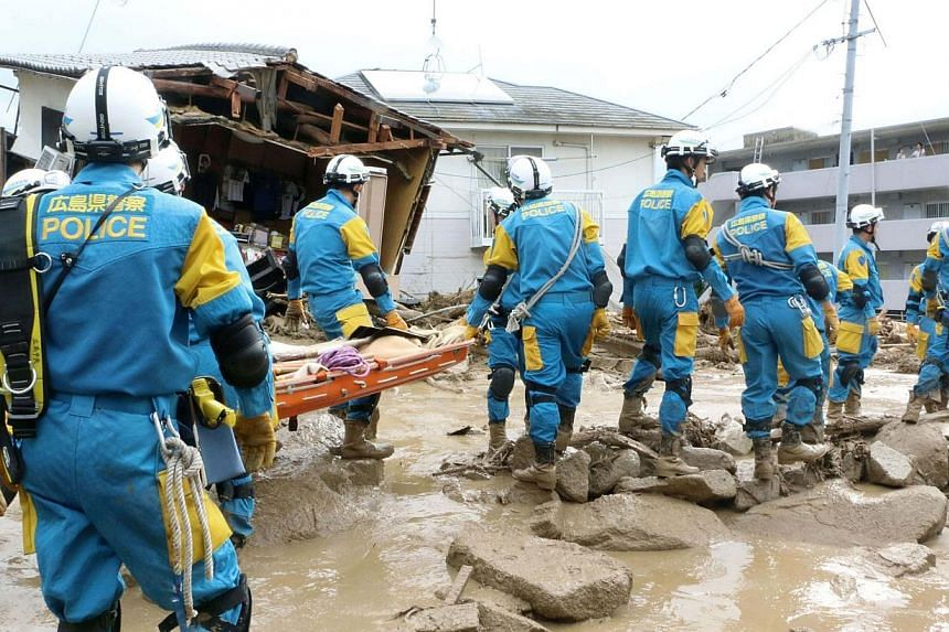 Rescue units of police officers walk during a rescue operation after a massive landslide swept through a residential area at Asaminami ward in Hiroshima, western Japan, in this photo taken by Kyodo on Aug 20, 2014.At least four people have been