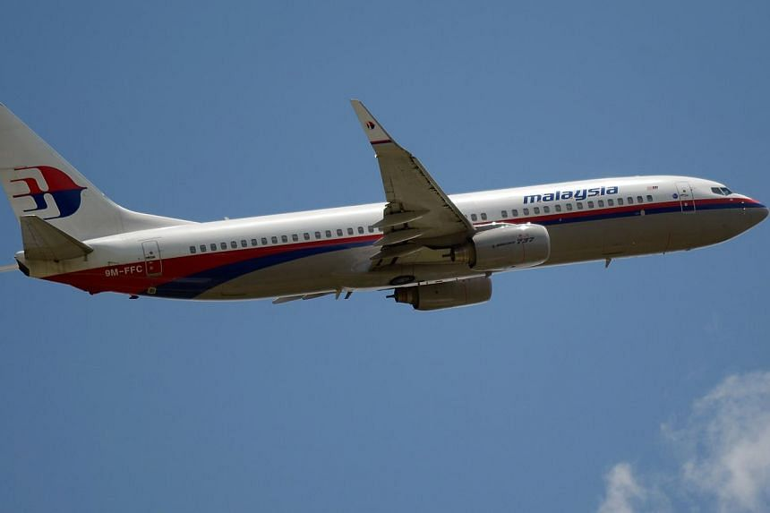 A file photo taken on March 18, 2013 shows a Malaysia Airlines Boeing 737 plane flying over the Sukarno-Hatta airport in Tangerang. -- PHOTO: AFP