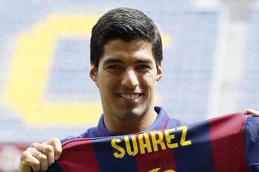 FC Barcelona's Luis Suarez holds up his jersey during his presentation at the Nou Camp stadium in Barcelona on Aug 19, 2014.Barcelona striker Luis Suarez said he has received professional help after receiving a four-month ban for biting an oppo