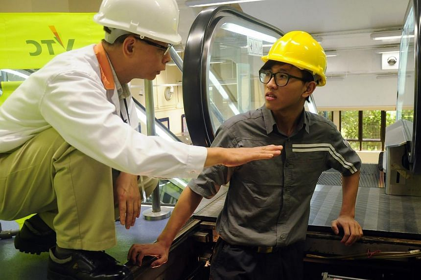 Trainee Wong Sheung Man (right) getting tips on how to repair a stuck escalator at the Vocational Training Council (VTC) campus. -- PHOTO: PEARL LIU