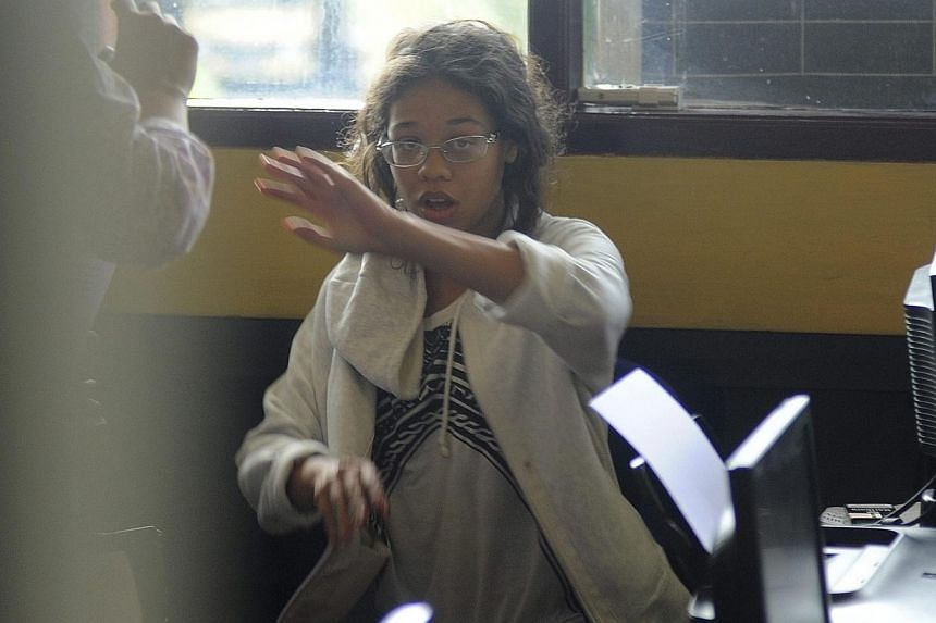 Heather Mack, the daughter of an American woman found dead inside a suitcase on Bali, gestures while in custody in a police station in Denpasar on Aug 14, 2014. Indonesia's National Police say it is possible that two United States citizens accus