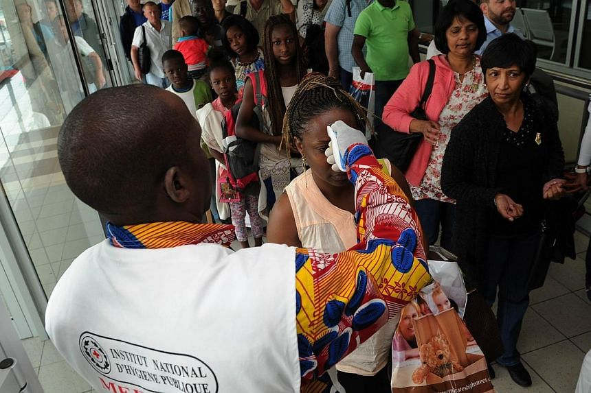 A doctor of the national public health institute controls the temperature of people at the airport, in Abidjan on Aug 13, 2014, as part of protective measures against the Ebola virus.South Africa on Thursday issued a ban on non-citizens travell