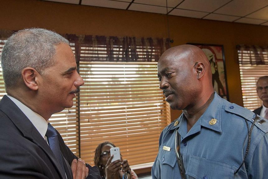 Attorney-General Eric Holder talks with Captain Ron Johnson of the Missouri State Highway Patrol at Drake's Place Restaurant in Florrissant, Missouri on Aug 20, 2014.Protests in the strife-torn town of Ferguson cooled late on Wednesday after th