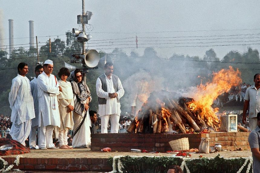 This photograph taken on Nov 3, 1984, shows India's then Premier Rajiv Gandhi (second from left), accompanied by his Italian-born wife Sonia (third from left), his daughter Priyanka (centre) and bodyguards as they stand at the cremation site of his m