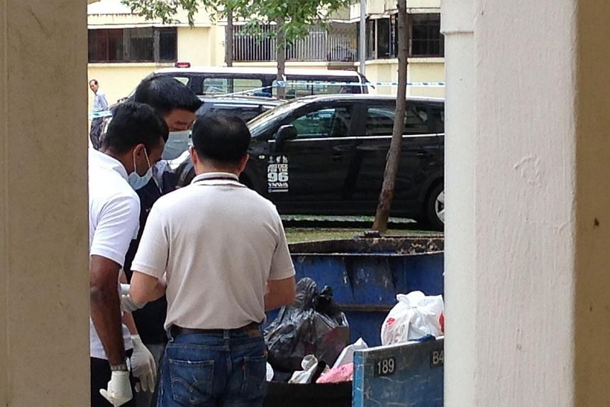Police investigators search through the rubbish chute for clues at the block where the murder happened. -- ST PHOTO: DANSON CHEONG