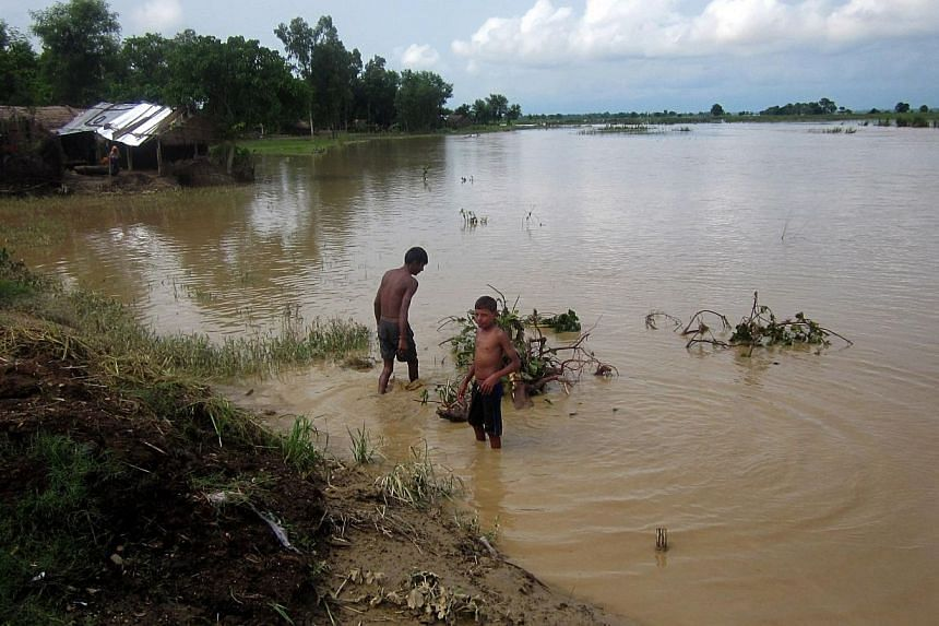In this photograph taken on Aug 16, 2014, Nepalese villagers walk through floodwaters in the village of Holiya in Banke District some 351km west of Kathmandu.A United States tourist died on Thursday while trying to cross a swollen river in Nepa