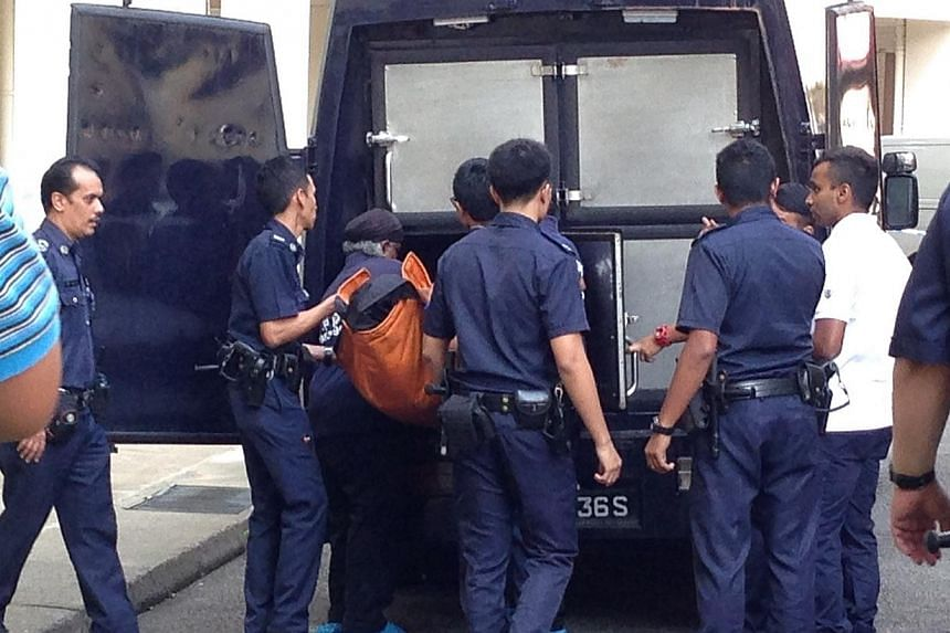 The body of a 54-year-old Chinese woman, who was killed on Thursday in her third-floor flat at Tampines Street 43, is brought out. -- ST PHOTO: DANSON CHEONG