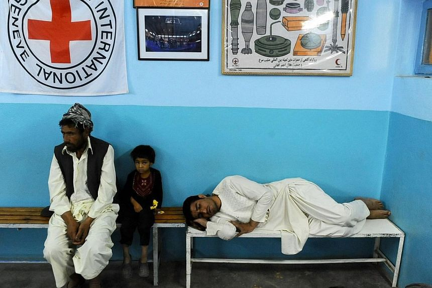 "Afghan patients wait on a benches at the Internatinal Committee of Red Cross ( ICRC) hospital for war victims in Herat province on Aug 17, 2014. One hundred and fifty years ago to the day, the first ""Geneva Convention for the Amelioration of the"