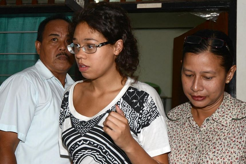 A police officer escorts suspect Heather Mack, 19, (centre) during an investigation at a police office in Nusa Dua on Indonesian resort island of Bali on Aug 13, 2014, after an American tourist's battered body was found in a suitcase at an exclusive