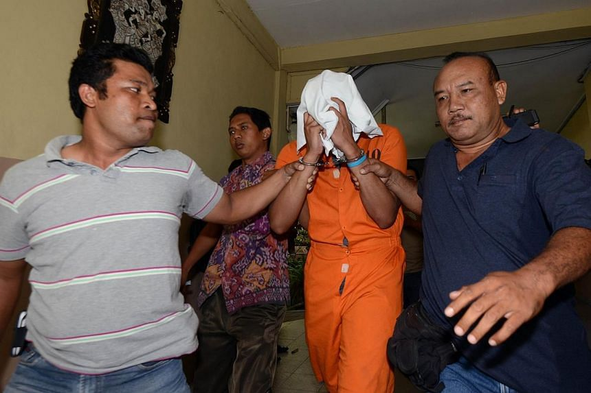 Police escort suspect Tommy Schaffer (centre), suspected in the murder of Sheila von Wiese Mack, while in custody at Bali police hospital in Denpasar on the Indonesian resort island of Bali on Aug 15, 2014. -- PHOTO: AFP
