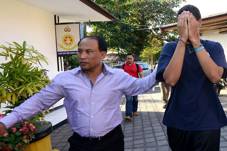 A police officer escorts suspect Tommy Schaefer, 21, (right) during an investigation at a police office in Nusa Dua on Indonesian resort island of Bali on Aug 13, 2014. -- PHOTO: AFP
