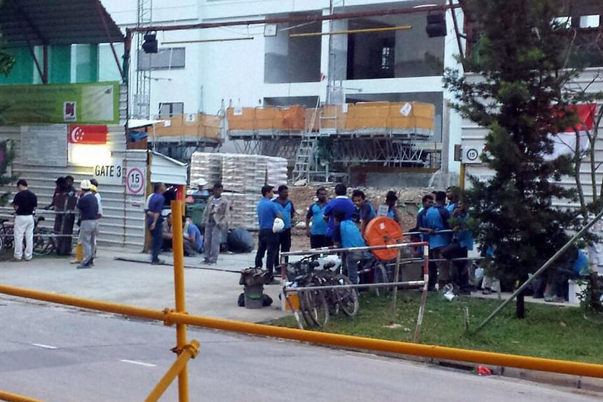 Workers gathering with their bags outside the Punggol dorm, on the site of a housing project, yesterday. The men said they were told to get ready to move to other dorms in Mandai and Kranji.