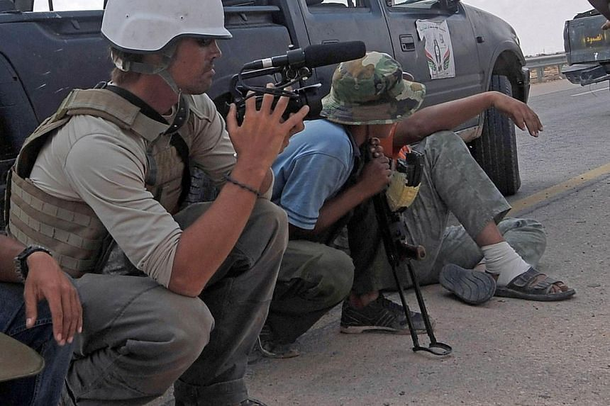 A file picture taken on Sept 29, 2011 shows US freelance reporter James Foley (left) on the highway between the airport and the West Gate of Sirte, Libya. Jihadist group the Islamic State claimed on Aug 19, 2014 to have executed Foley in revenge for