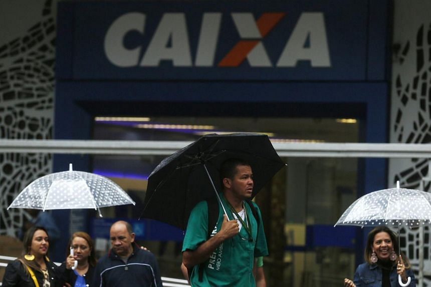 People walk past a Caixa Economica Federal bank in downtown Rio de Janeiro August 14, 2014. Banks in Brazil will be allowed to use up to 60 per cent of reserves for credit operations, an increase from the 50 per cent limit announced on July 25.