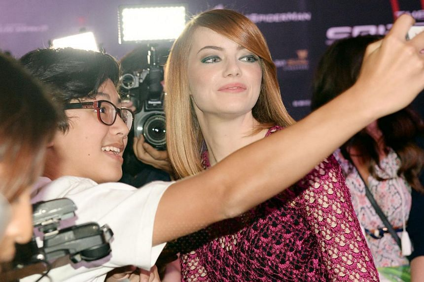 Hollywood actress Emma Stone (right) posing for a selfie with a fan on the red carpet during the film premiere of The Amazing Spider-Man 2: Rise of Electro at Marina Bay Sands in Singapore on 27 March 2014. -- PHOTO: BERITA HARIAN FILE