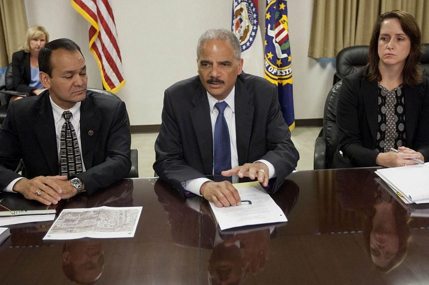 US Attorney General Eric Holder (centre) during his meeting with Special Agent in Charge William P. Woods (left) and Acting Assistant Attorney General for Civil Rights Molly Moran at the FBI building in St. Louis, Missouri. -- PHOTO: AFP