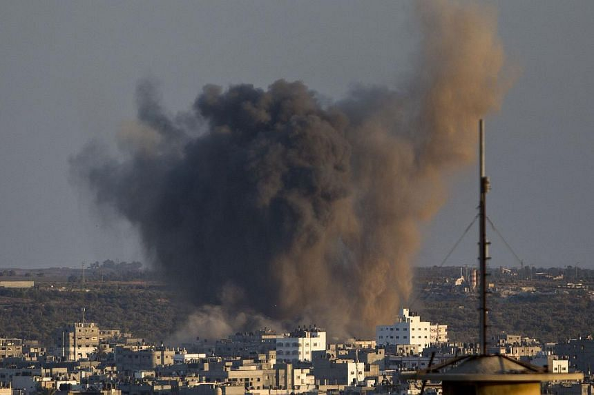 Smoke rises from buildings following an Israeli air strike on Gaza City on August 20, 2014. Israeli warplanes pounded Gaza as furious mourners buried the wife and child of Hamas' top military commander, baying for revenge as nine days of calm explode