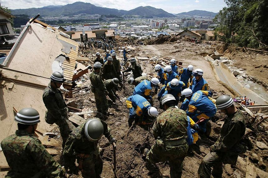 Japan Self-Defense Force (JSDF) soldiers and police officers search for survivors at a site where a landslide swept through a residential area at Asaminami ward in Hiroshima, western Japan, on Aug 21, 2014. -- PHOTO: REUTERS