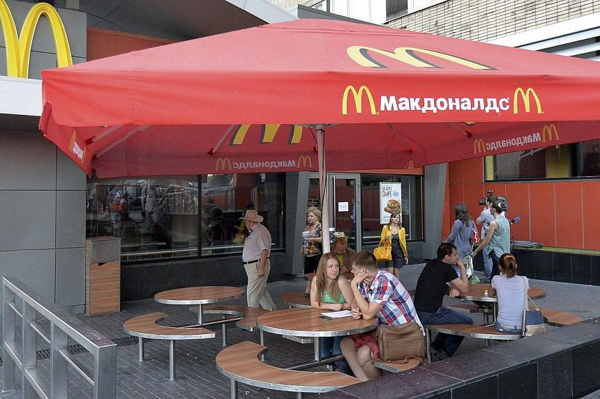 People sit outside a closed McDonald's restaurant in Moscow, August 20, 2014. Russia ordered the temporary closure of four McDonald's restaurants in Moscow on Wednesday, a decision it said was over sanitary violations but which comes against a backdr