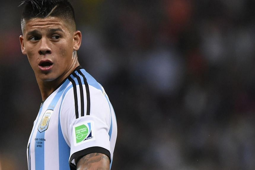 In this file picture taken on July 9, 2014, Argentina's defender Marcos Rojo reacts during the second half of extra time during the semi-final football match between Netherlands and Argentina at the FIFA World Cup in Sao Paulo. Manchester United on W