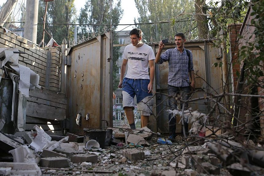 People walk in front of a building damaged by, what locals say, was recent shelling by Ukrainian forces in Donetsk on August 20, 2014. -- PHOTO: REUTERS