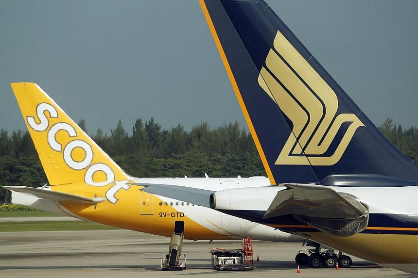 A Scoot and a Singapore Airlines (SIA) plane at Changi Airport Terminal 2. -- ST PHOTO: LIM WUI LIANG
