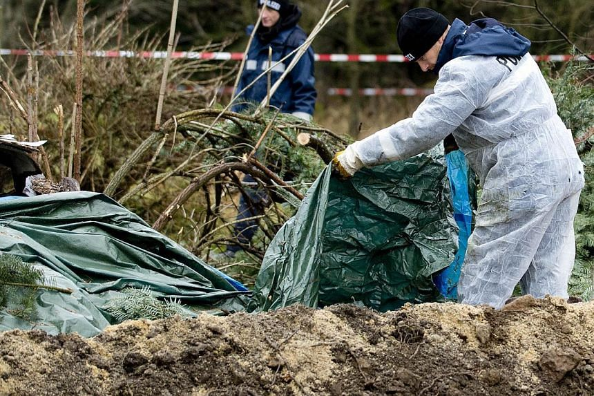 Policemen search for evidence at the area where body parts were found on Nov 29, 2013 in Reichenau, eastern Germany. A German police officer will go on trial on Aug 22, 2014, accused of murdering a volunteer he met on a website for cannibalism fetish