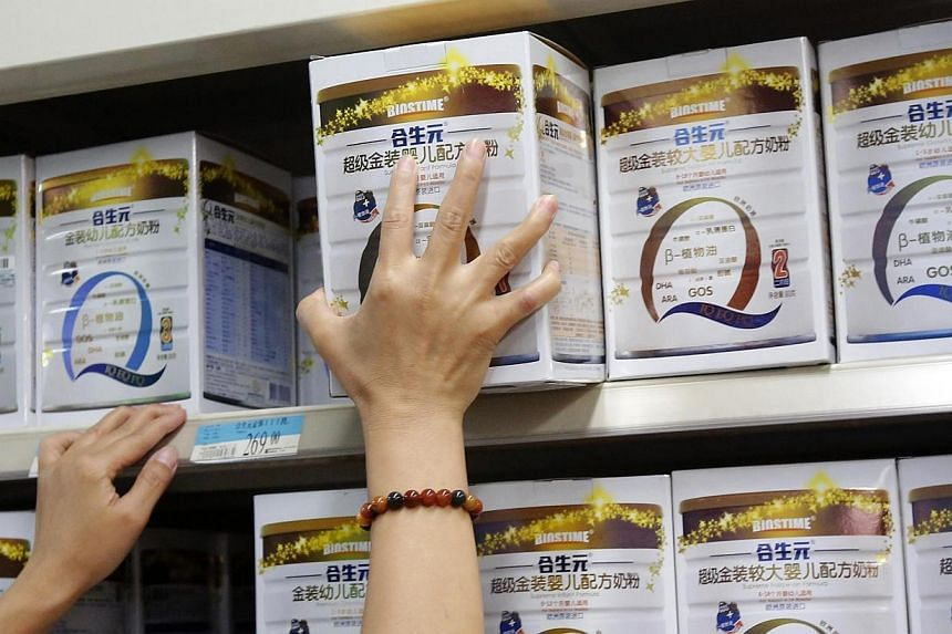A store assistant arranges Biostime's milk powder products on a shelf at a supermarket in Beijing on Aug 7, 2013.A Chinese retailer is offering insurance to customers who buy infant milk powder, highlighting the lengths to which companies are g