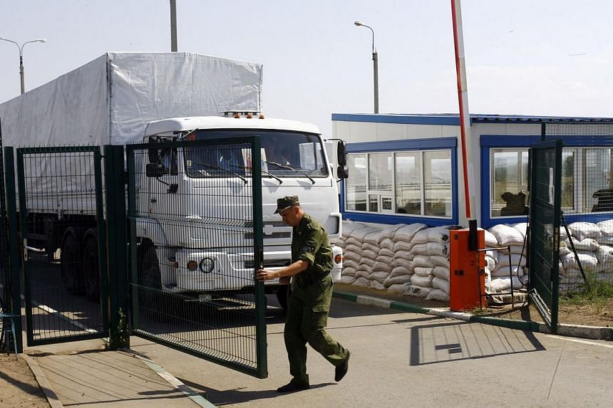 A man opens the gate to let lorries, part of a Russian humanitarian convoy, cross the Ukrainian border at the Izvarino custom control checkpoint on Aug 22, 2014.Ukraine on Friday, Aug 22, 2014, accused Moscow of invading after Russia unilateral