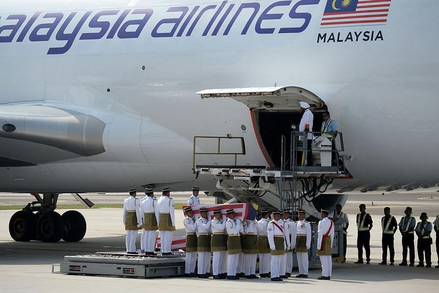 Soldiers carry a coffin with the remains of a Malaysian victim from the Malaysia Airlines flight MH17 that crashed in Ukraine during a ceremony at the Bunga Raya complex at the Kuala Lumpur International Airport in Sepang on Aug 22, 2014. -- PHOTO: A