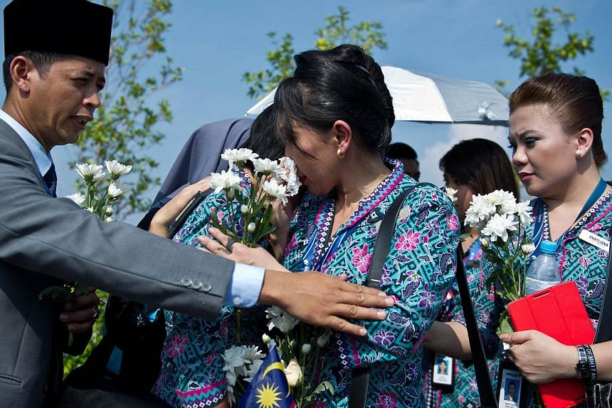 Malaysia Airlines flight attendants cry during the arrival of the remains of Malaysians who perished aboard flight MH17 that was downed in eastern Ukraine outside Bunga Raya complex in Sepang on Aug 22, 2014. -- PHOTO: AFP