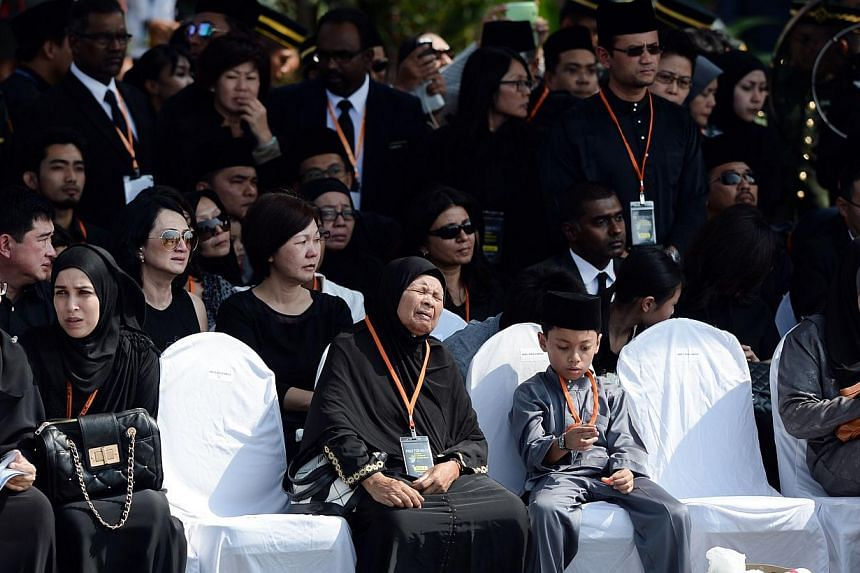 Relatives attend a ceremony for the return of the remains of Malaysian victims from the Malaysia Airlines flight MH17 that crashed in Ukraine at the Bunga Raya complex at the Kuala Lumpur International Airport in Sepang on Aug 22, 2014. -- PHOTO: AFP