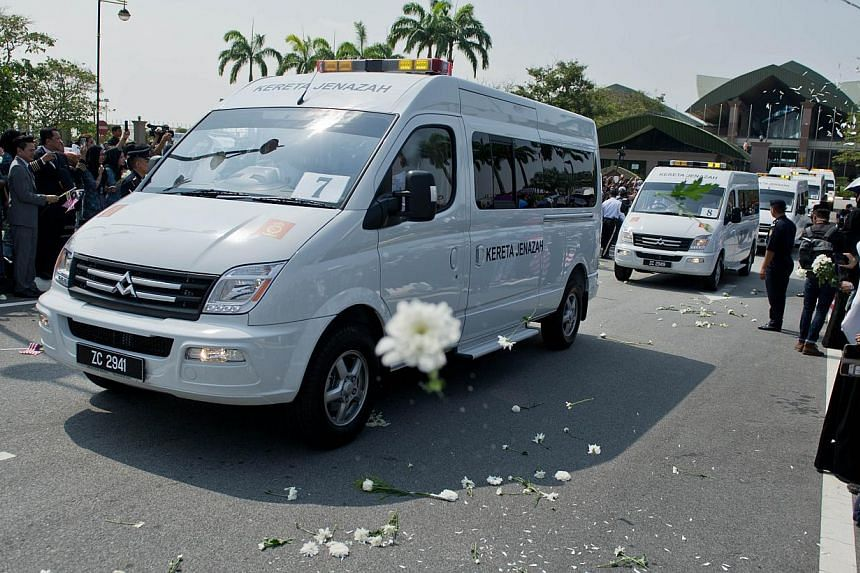Malaysia Airlines flight attendants (unseen) throw white flowers as a convoy of hearses carrying the remains of the victims of Malaysia Airlines flight MH17 at the Bunga Raya complex in Sepang on Aug 22, 2014. -- PHOTO: AFP