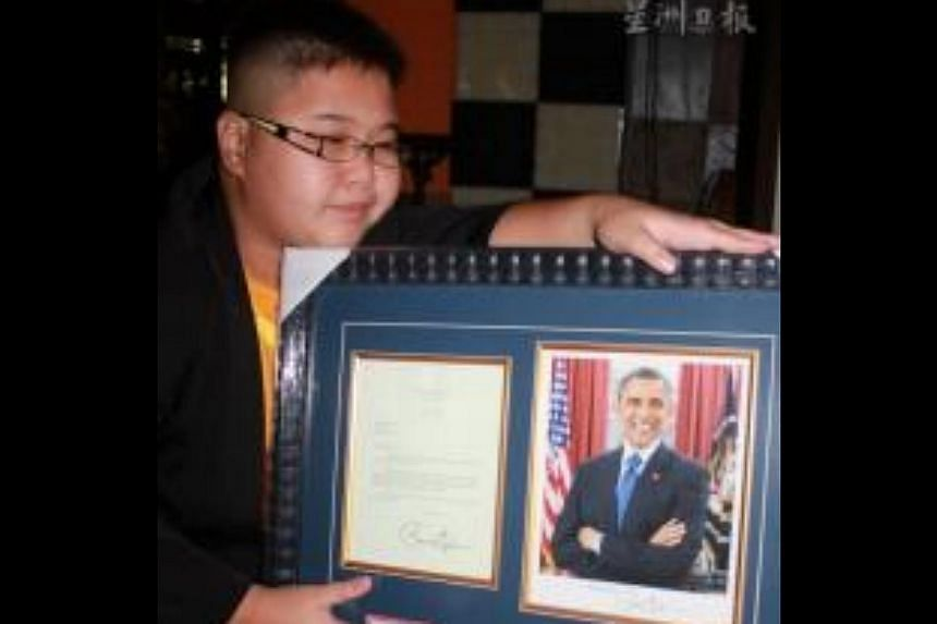 Delwin Cheah Wien Loong, 11, with the framed letter from US President Barack Obama-- PHOTO: SIN CHEW DAILY/ASIA NEWS NETWORK
